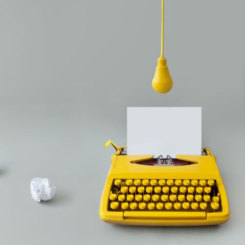 Yellow typewriter with a lightbulb above it and a crumpled wad of paper next to it