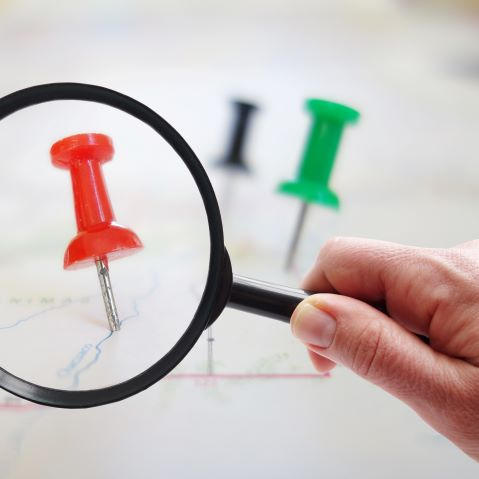 A magnifying glass looking at an enlarged pin on a map, representing how Google Local Services ads can highlight law firms in their own city