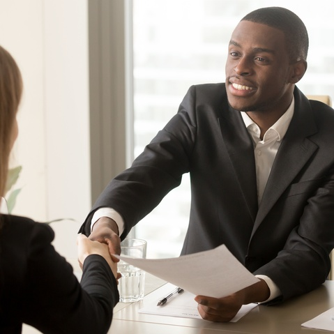 Two male lawyers are meeting with a female client. One of the lawyers is shaking the clients hand and smiling at them.
